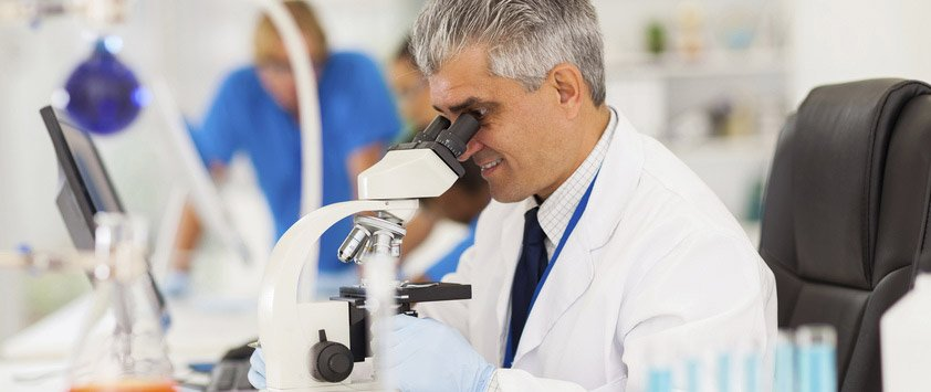 pathologist in lab looking into a microscope