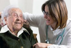 happy VNA nurse at home with elderly patient