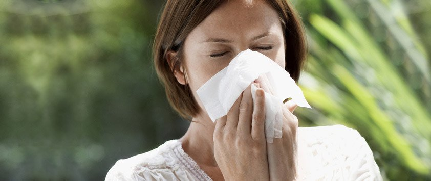 allergies, women sneezing into a tissue